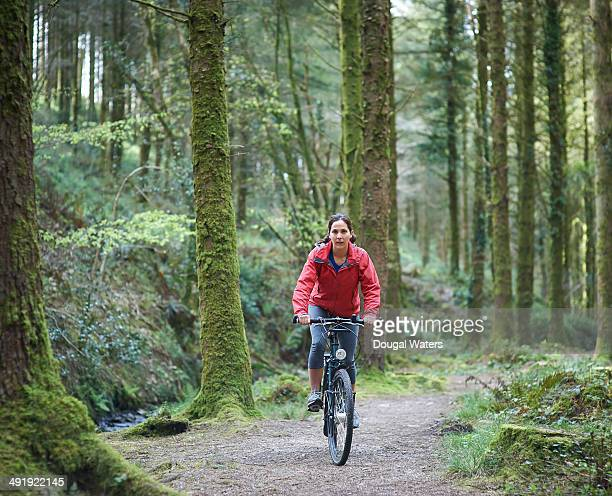Cyclist riding mountain bike along path in forest.