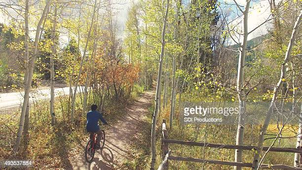 Cyclist riding on dirt trail in Colorado mountain foothills