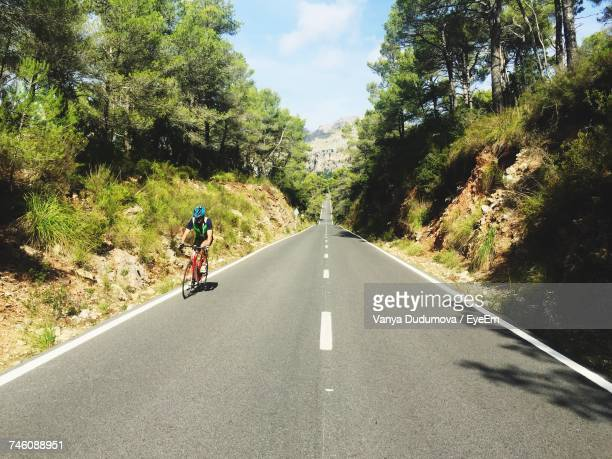 Cyclist Riding On Road During Sunny Day