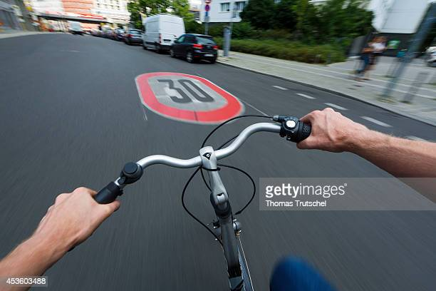 Cyclist riding over a 30 km/h speed limit sign which is painted on the street on August 05 in Berlin Germany Pedestrians and cyclists are...