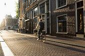 Cyclist riding through cobbled street, Amsterdam, Netherlands
