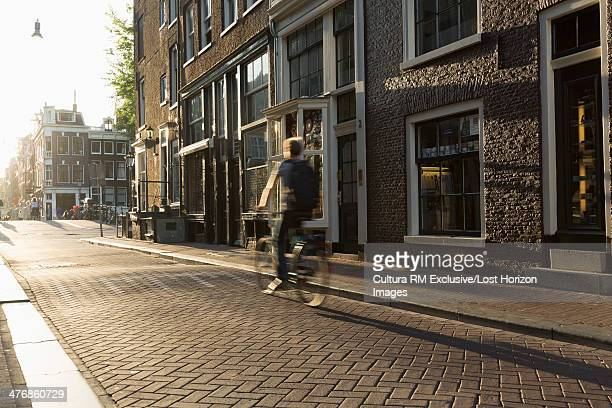 Cyclist riding through cobbled street, Amsterdam, Netherlands