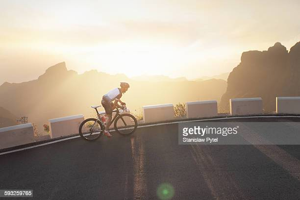 Cyclist riding up at sunset , mountains around