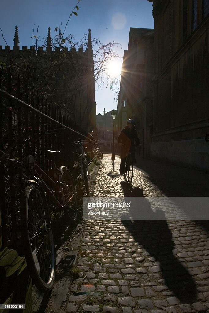 A cyclist silhouetted against the winter sun enters Radcliffe Square Oxford from St Mary's Passage Affectionately named 'the city of dreaming spires'...