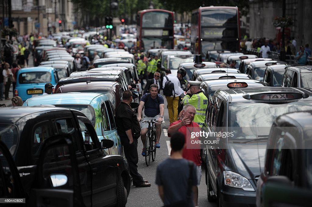 A cyclist squeezes through the corridor between lines of parked taxis blocking a street during a protest by London black cab drivers against a new private taxi service 'Uber', a mobile phone app, in central London on June 11, 2014. Taxi drivers brought parts of London, Paris and other European cities to a standstill on June 11 as they protested against new private cab apps such as Uber which have shaken up the industry. Thousands of London's iconic black cabs, many of them beeping their horns, filled the roads around Buckingham Palace, Trafalgar Square and the Houses of Parliament to the exclusion of any other vehicles.