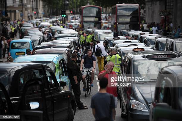A cyclist squeezes through the corridor between lines of parked taxis blocking a street during a protest by London Black Cab drivers against a new...