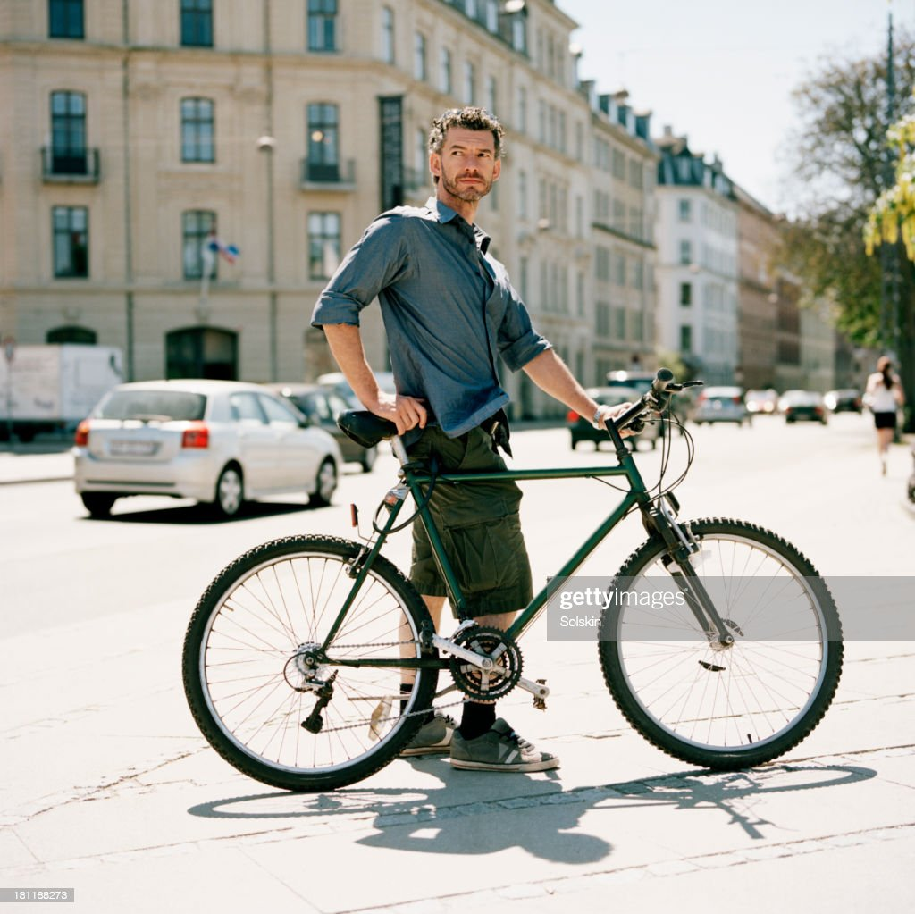 cyclist standing in city surroundings