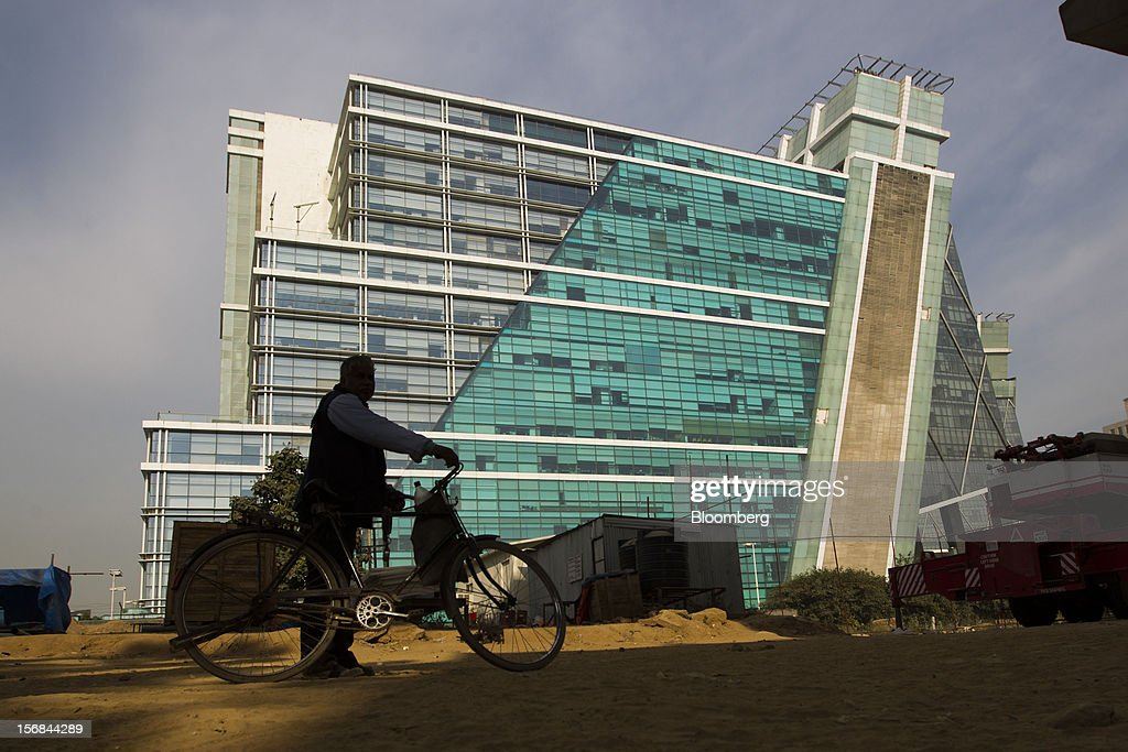 A cyclist stands in front of a glass building in the DLF Cyber City in Gurgaon, India, on Wednesday, Nov. 21, 2012. Indian Prime Minister Manmohan Singh aims to spur spending on infrastructure to revive a faltering economy and tackle bottlenecks contributing to one of Asia's highest inflation rates. Photographer: Brent Lewin/Bloomberg via Getty Images