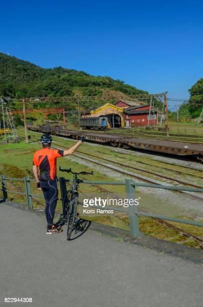 Cyclist stopped admiring the paranapiacaba railroad yard in são paulo brazil