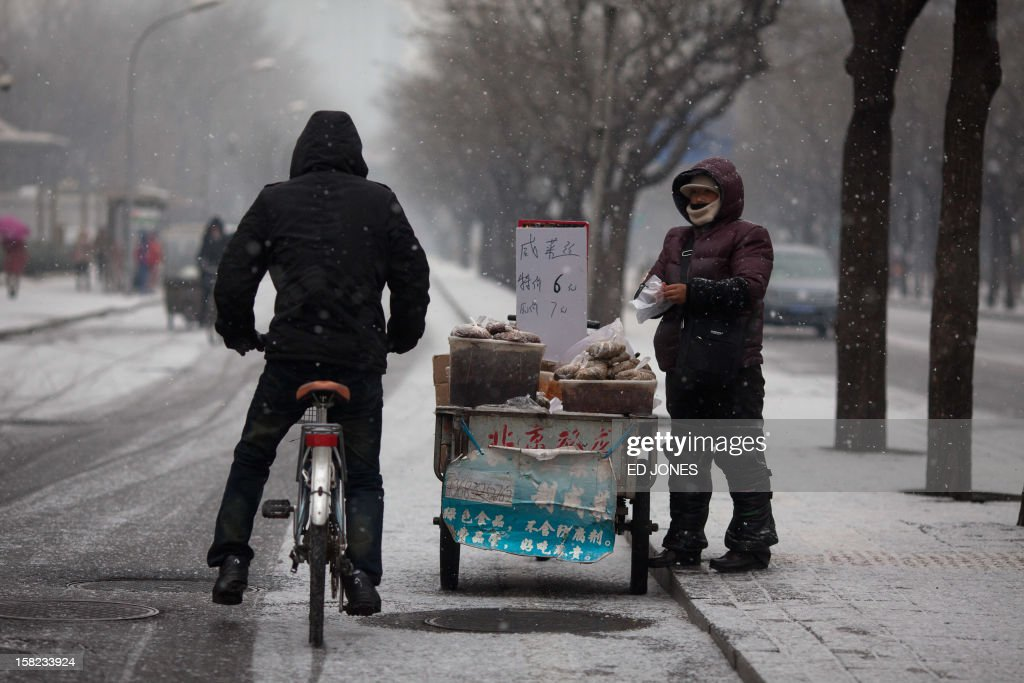 A cyclist stops at a hot potato stand during snowfall in Beijing on December 12, 2012. Snowfall hit the Chinese capital with seasonal minus temperatures forecast to bring more later in the week. AFP PHOTO / Ed Jones