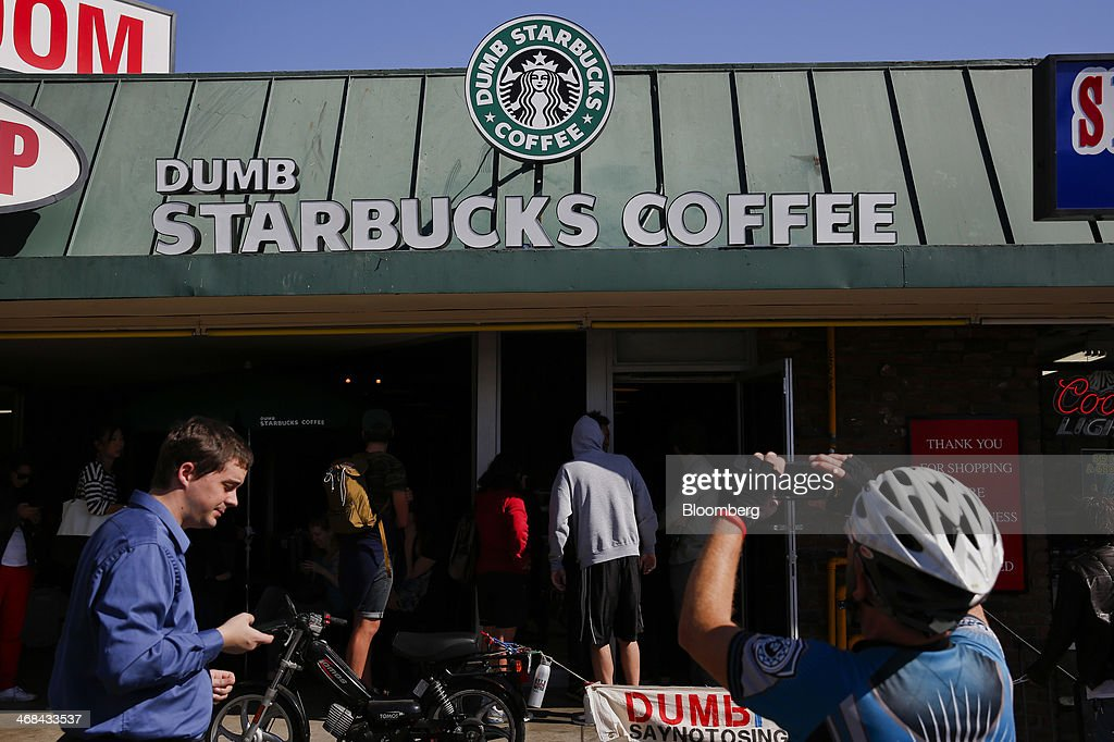 A cyclist takes a photograph while customers wait in line to enter the Dumb Starbucks Coffee store, a parody of the Starbucks Corp. coffee chain, in Los Angeles, California, U.S., on Monday, Feb. 10, 2014. Dumb Starbucks, which opened this past weekend, offered Dumb Vanilla Blonde Roast, Dumb Chai Tea Latte, and Dumb Caramel Macchiato, all available in sizes Dumb Venti, Dumb Grande, and Dumb Tall. Photographer: Patrick T. Fallon/Bloomberg via Getty Images