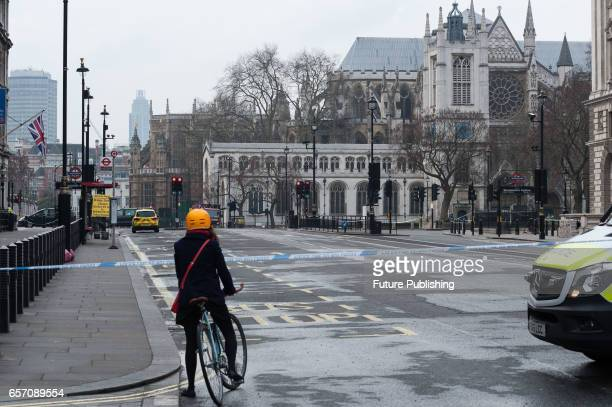 A cyclist tries to commute across cordoned off area around the Houses of Parliament on a day after a terrorist attack on March 23 2017 in London...
