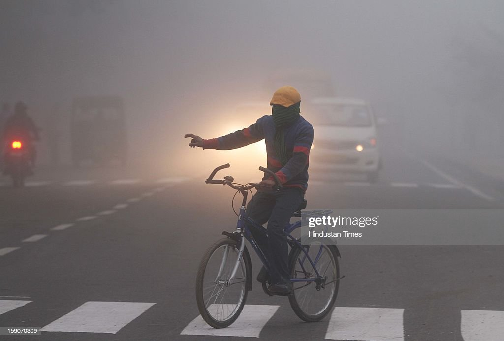 A cyclist trying to cross the street on a foggy and cold morning on January 7, 2013 in New Delhi, India. Dense fog and icy winds disrupted normal life as Delhi's minimum temperature settled at five notches below average at 2.4 degrees Celsius. Fog forced visibility to drop to about 500 metres in the morning resulting in 15 flights and 42 trains were delayed out of Delhi while 18 trains got cancelled.