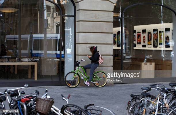 A cyclist uses a mobile device outside the Apple Inc store in Amsterdam Netherlands on Monday Sept 16 2013 While the cheaper of Apple Inc's new...