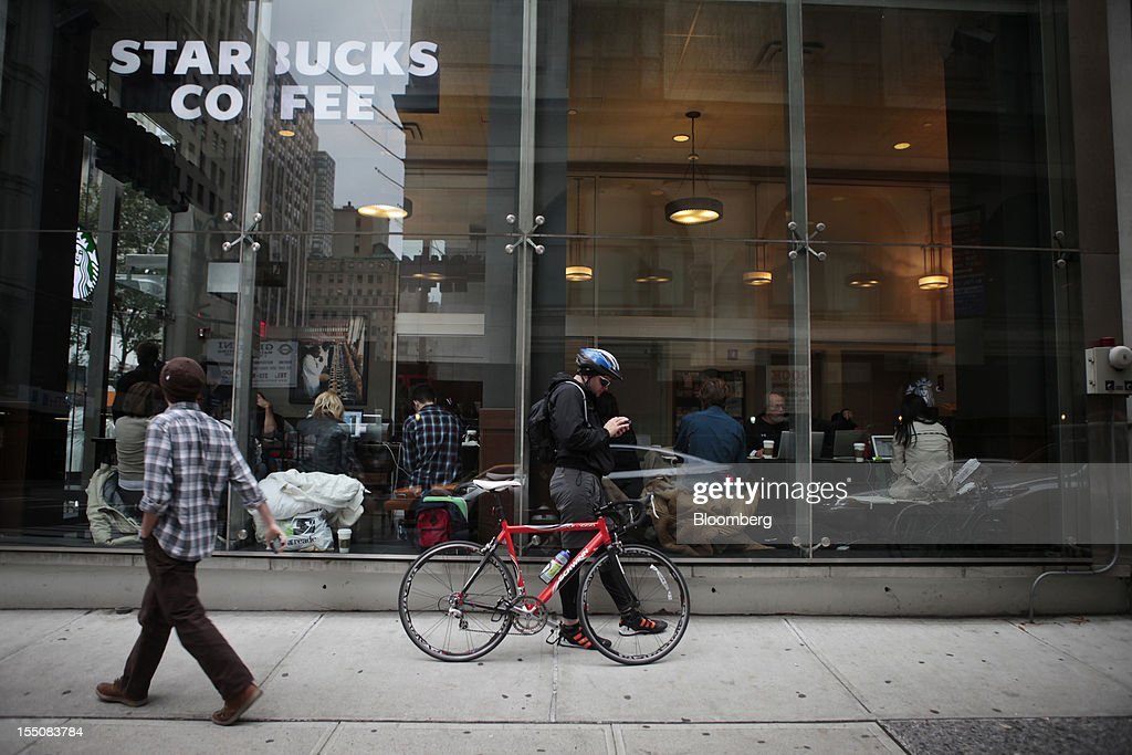 A cyclist uses his mobile device outside a Starbucks Corp. store as customers sit with their laptop computers inside on Fifth Avenue in midtown Manhattan in New York, U.S., on Wednesday, Oct. 31, 2012. Atlantic superstorm Sandy may cut U.S. economic growth as it keeps millions of employees away from work and shuts businesses from restaurants to refineries in one of the nation's most populated and productive regions. Photographer: Victor J. Blue/Bloomberg via Getty Images
