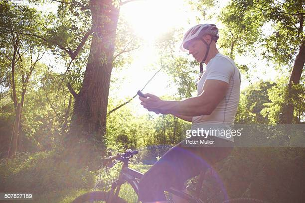 Cyclist using smartphone in forest