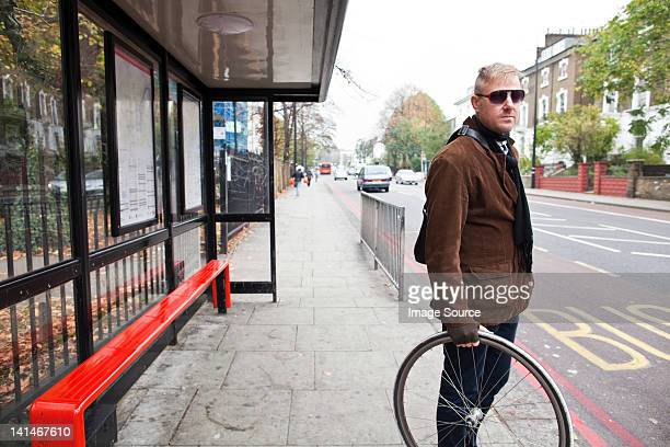 Cyclist waiting at bus stop