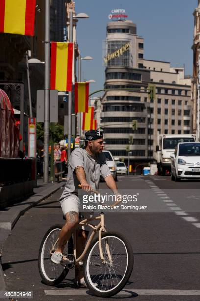A cyclist waits at a traffic light at Gran Via as Spanish flags hang from lampposts the day before Prince Felipe's coronation on June 18 2014 in...