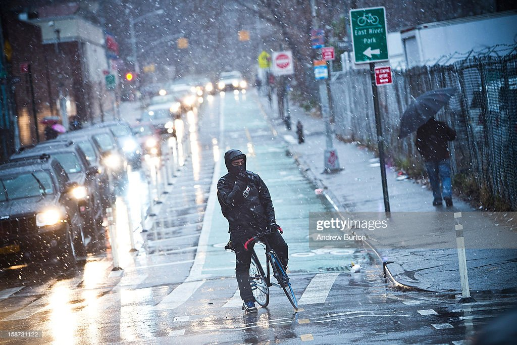 A cyclist waits to cross the street while a winter snow storm hits the region on December 26, 2012 in New York City. Snow, mixed with and changing to rain, is expected to hit the New York City area this afternoon into the evening.