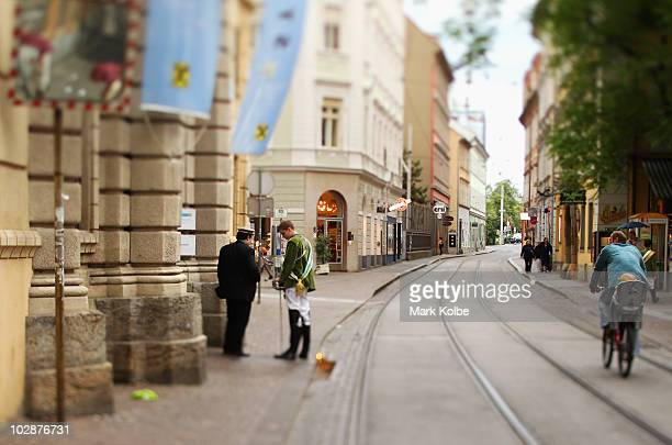A cyclist watches on as he passes two men in soldiers uniforms speaking in the street on May 29 2010 in Graz Austria