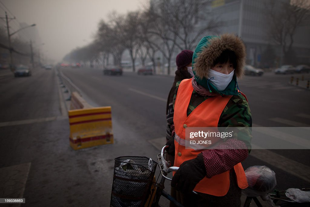 A cyclist wearing a mask prepares to cross a road during severe pollution in Beijing on January 12, 2013. Air quality data released via the US embassy twitter feed recorded air quality index levels so hazardous that they were classed as 'Beyond Index'. By 4pm the particle matter (PM) 2.5 figure was 728 on a scale that stops at 500 at which point the US embassy website advises against all outdoor activity. AFP PHOTO / Ed Jones
