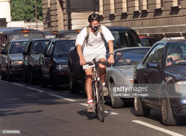 A cyclist wearing an antipollution mask overtakes queues of vehicles on the streets of London on the day that the government publishes its National...