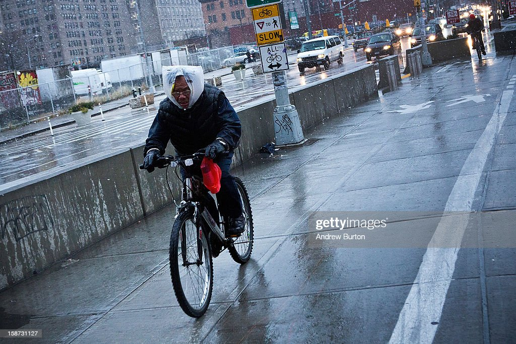 A cyclist wears a plastic bag on his head to protect himself from winter snow on December 26, 2012 in New York City. Snow, mixed with and changing to rain, is expected to hit the New York City area this afternoon into the evening.