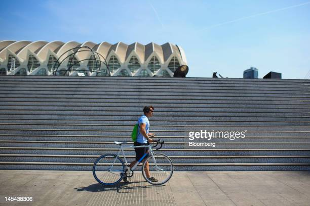 A cyclist wheels his bicycle past the Prince Felipe Science Museum at the City of Arts and Sciences in Valencia Spain on Tuesday May 29 2012 The...