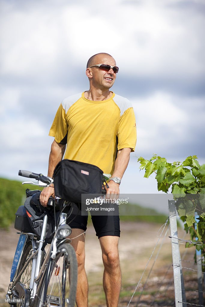 Cyclist with map in vineyard : Stock Photo