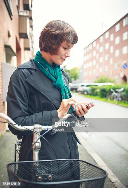 Cyclist with smartphone in Copenhagen, Denmark.