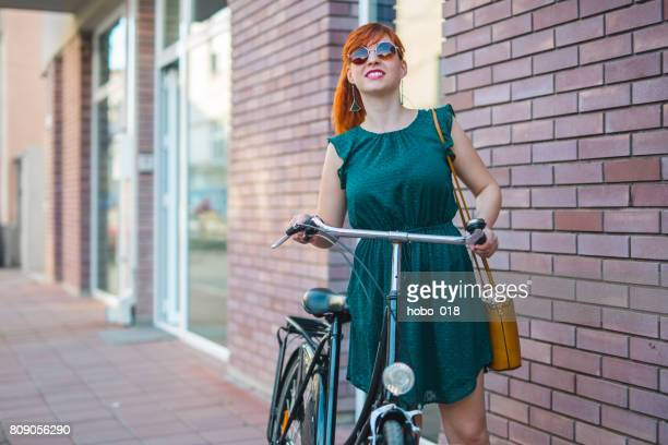 Cyclist woman posing against red brick wall