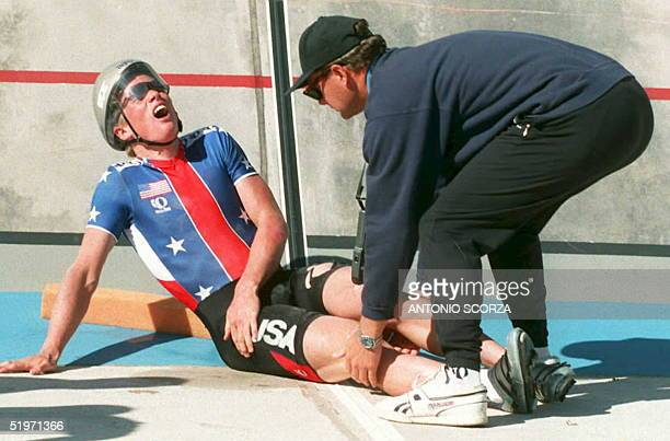 US cyclist Zachary Conrad is checked for injuries by an unidentified US trainer after taking a spill during a qualifying round in the men's 4 km team...
