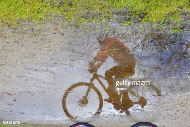 Cyclista reflected in a puddle of water