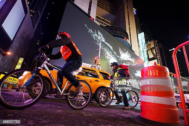 Cyclists and a vehicle pass Vornado Realty Trust's 330foot digital billboard wrapped around the front of the Marriott Marquis Hotel on Broadway...