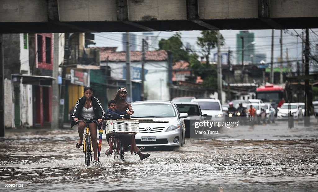 Cyclists and cars pass through a flooded street after heavy rains on May 30, 2016 in Recife, Brazil. Lack of proper drainage in areas is one of many contributing factors leading to mosquito-borne illnesses in the city, including the Zika virus. Microcephaly is a birth defect linked to the Zika virus where infants are born with abnormally small heads. The city of Recife and surrounding Pernambuco state remain the epicenter of the Zika virus outbreak, which has now spread to many countries in the Americas. A group of health experts recently called for the Rio 2016 Olympic Games to be postponed or cancelled due to the Zika threat but the WHO (World Health Organization) rejected the proposal. The Olympic torch passes through Recife May 31.