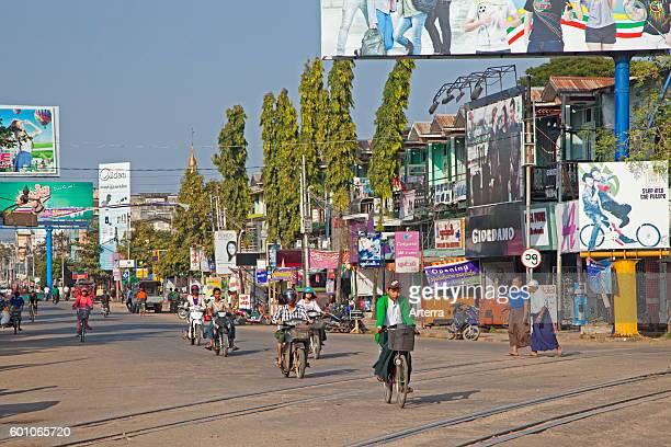 Cyclists and motorbike riders in shopping street in Pyay / Prome Bago Region Myanmar / Burma