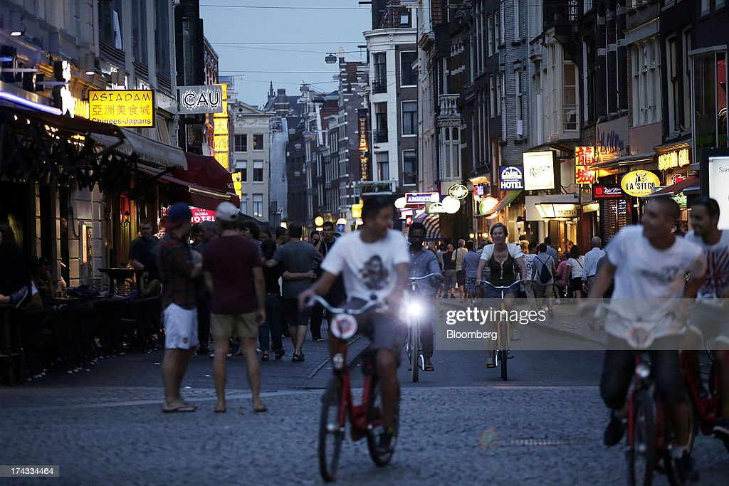 Cyclists and pedestrians pass restaurants on a street at night in Amsterdam, Netherlands, on Tuesday, July 23, 2013. Dutch pension funds will be allowed to calculate liabilities on the basis of an adjusted discount rate as the government seeks to keep the retirement system viable amid low interest rates and an aging population. Photographer: Matthew Lloyd/Bloomberg via Getty Images