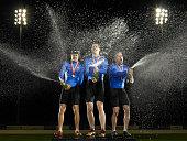 Cyclists celebrating, spraying champagne