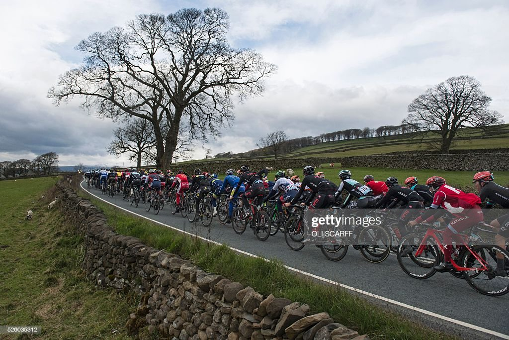Cyclists competing in the first stage of the Tour de Yorkshire pass through Long Preston in northern England, on April 29, 2016. / AFP / OLI
