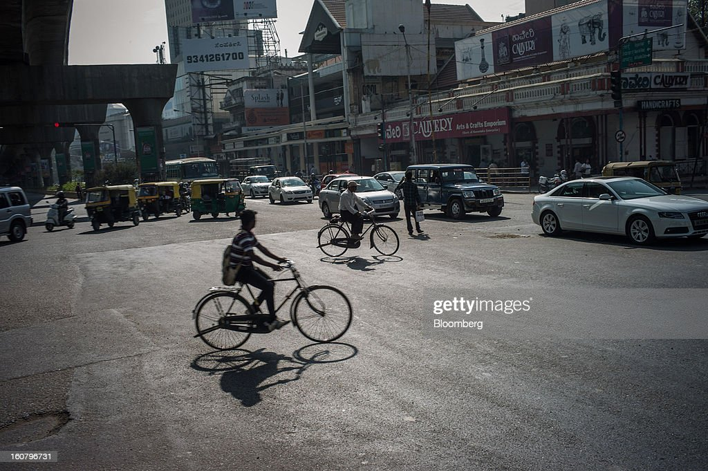 Cyclists cross an intersection at Mahatma Gandhi Road in Bangalore, India, on Monday, Feb. 4, 2013. India's monetary authority predicted that the economy will expand 5.5 percent in the year ending March 31, which would be the smallest gain since 2003. Photographer: Sanjit Das/Bloomberg via Getty Images