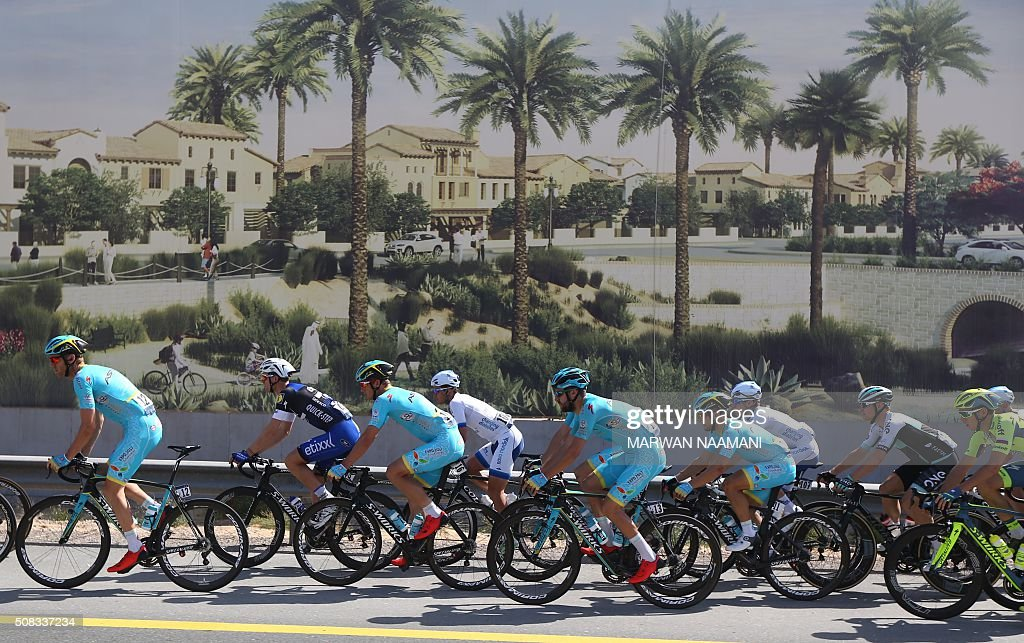 Cyclists cycle past an advertisement billboard during the second stage of Dubai Tour 2016 in Dubai on February 4, 2016. Italy's Elia Viviani, riding for Team Sky, sprinted to victory in the second stage of the Tour of Dubai and grabbed the leader's blue jersey from Germany's Marcel Kittel. Viviani had benefitted from a crash in the final kilometre that appeared to affect opponents. NAAMANI