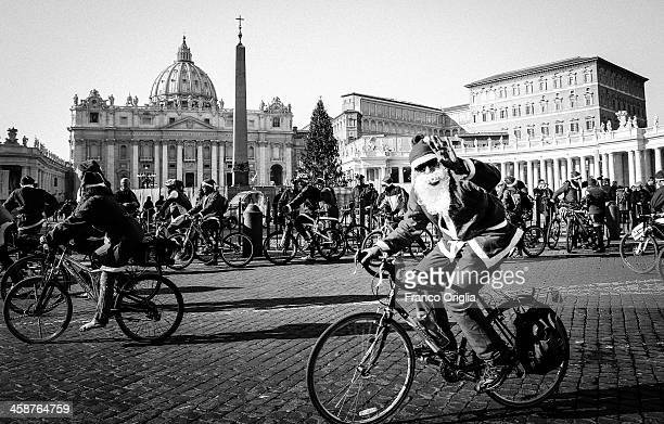 Cyclists dressed up as Santa Claus appear in St Peter's Square on December 21 2013 in Vatican City Vatican