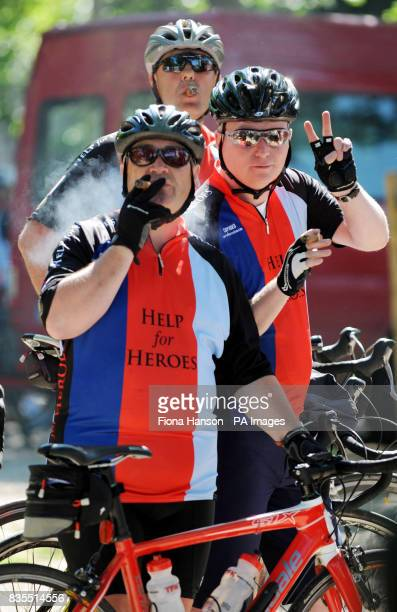 Cyclists from the Help for Heroes Band of Brothers bike enjoy a cigar after attending a wreath laying ceremony at the Arc de Triomphe Paris before...