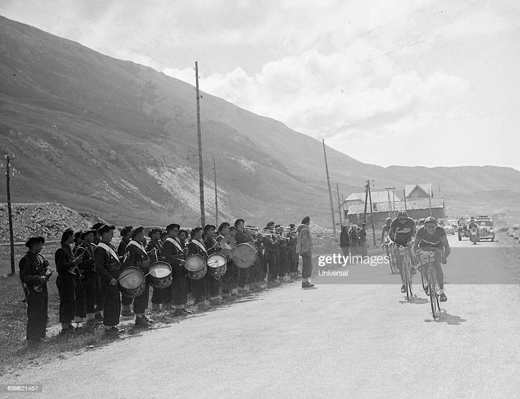 Cyclists Gino Bartali and Fausto Coppi pass a marching band. They are leading the pack in the 17th stage (between Aosta, Italy and Briancon, France) of the 1949 Tour de France. The area in which they are racing is the Petit Saint-Bernard's Pass. | Location: Between Briancon, France and Aosta, Italy.