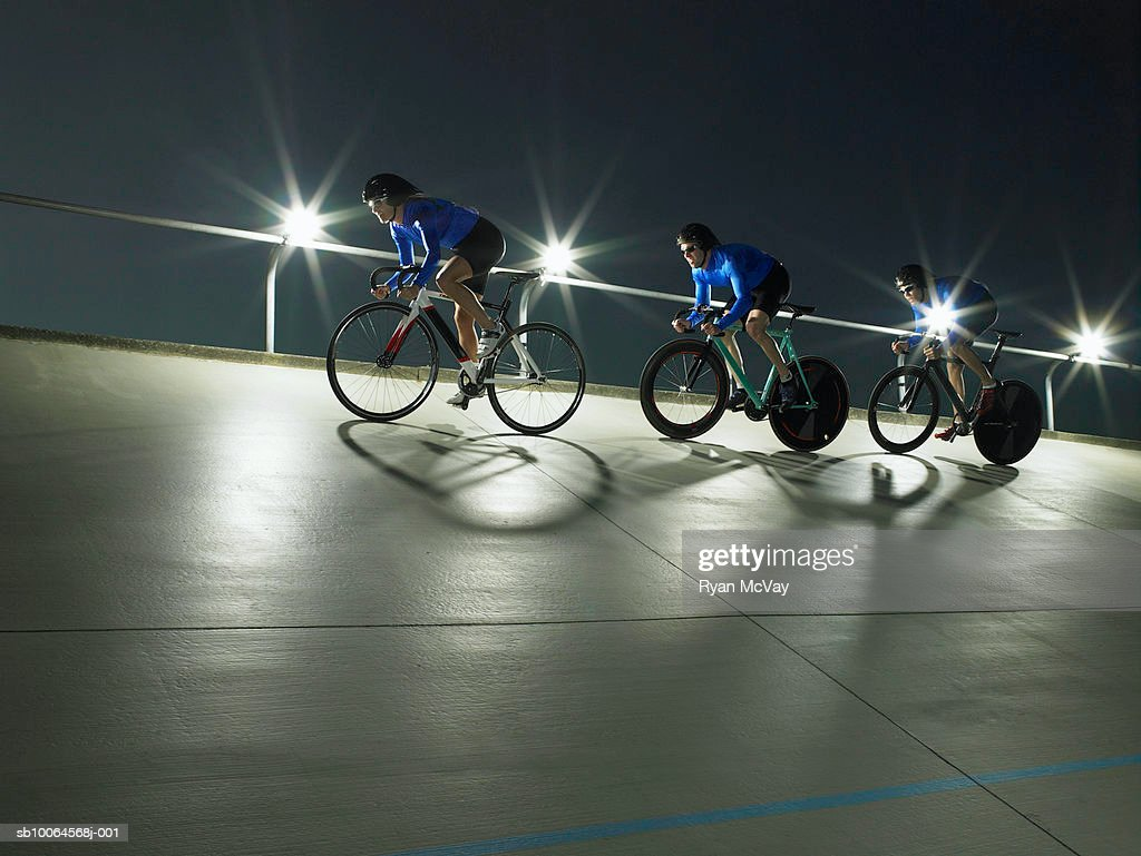 Cyclists in action on velodrome track, low angle view