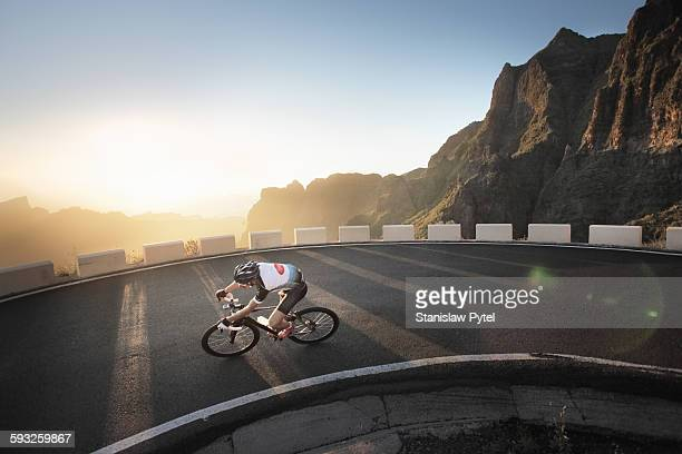 Cyclists making a turn in mountains at sunset