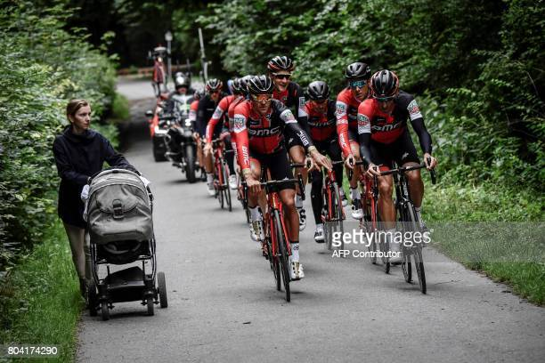 TOPSHOT Cyclists of the USA's BMC Racing cycling team ride past a woman pushing a stroller during a training session in Dusseldorf Germany on June 30...