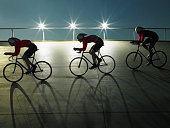 Cyclists on velodrome track at night, side view