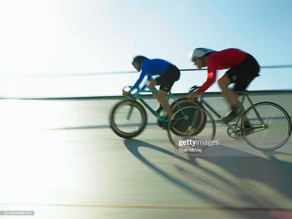 Cyclists on velodrome track, side view (blurred motion)
