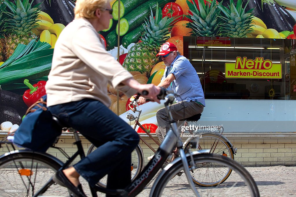 Cyclists pass a giant poster showing fruit and vegetables on the window of a Netto supermarket, operated by Netto Supermarket GmbH & Co., in Berlin, Germany, on Thursday, April 18, 2013. Germany's economy is shrugging off a contraction at the end of last year and starting to grow due to revived exports and rising private consumption, the country's leading economic institutes said. Photographer: Krisztian Bocsi/Bloomberg via Getty Images